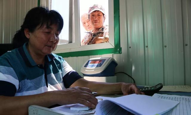 """北京平谷刘家店镇的""""生态桥""""工程试点基地工作人员(左)给果农们开具废弃枝条称重单"""